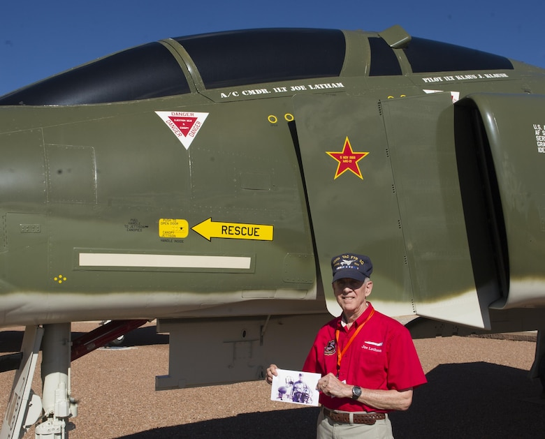 Col. (Ret.) Joe Latham, previously an F-4 Phantom pilot from Holloman Air Force Base, N.M., poses for a picture with an old photo as a first lieutenant in 1966, next to an F-4 adorned with his name Sept. 13, 2016, at Heritage Park, Holloman AFB. Latham's visit was part of the annual Phantom Society Tour where 160 aircraft enthusiasts, including veterans and non-veterans with aviation backgrounds, toured The tour included an F-16 Fighting Falcon static display and briefing, travel to Holloman's High Speed Test Track, the opportunity to view QF-4 Phantom IIs and F-16s in flight, and a visit to the base's heritage park to view static displays of various aircraft historically stationed at Holloman AFB. (U.S. Air Force photo/Master Sgt. Matthew McGovern)
