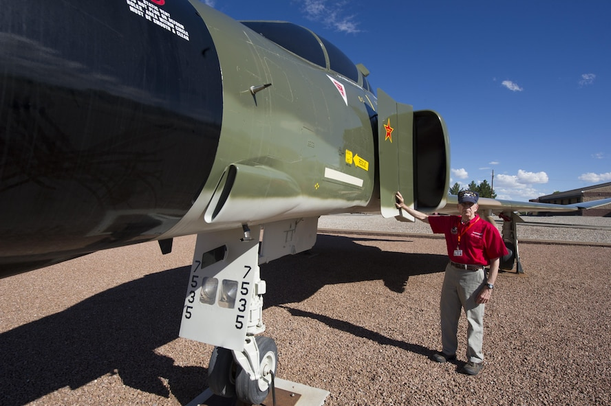 Col. (Ret.) Joe Latham, previously an F-4 Phantom pilot from Holloman Air Force Base, N.M., poses for a picture Sept. 13, 2016, at Heritage Park, Holloman AFB, next to an F-4 adorned with his name. Latham shot down a MiG-21 35 miles north of Hanoi, Vietnam on Nov. 5, 1966. Latham's visit was part of Holloman's annual Phantom Society Tour where 160 aircraft enthusiasts, including veterans and non-veterans with aviation backgrounds, visit various base locations. The tour included an F-16 Fighting Falcon briefing and static display, travel to Holloman's High Speed Test Track, the opportunity to view QF-4s and F-16s in flight, and a visit to Heritage Park to view displays of various aircraft historically stationed at Holloman AFB. (U.S. Air Force photo by Master Sgt. Matthew McGovern)