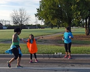 U.S. Air Force Staff Sgt. Marcela Huerta, 7th Force Support Squadron fitness assessment cell manager, watches as her daughter, Akira, gives water and directions to Mica Jones, personal trainer and fitness instructor, during the Dyess Mini Marathon at Dyess Air Force Base, Texas, Sept. 17, 2016. More than 15 volunteers were present at several checkpoints to assist over 50 participants by providing water and directions for each particular race route. (U.S. Air Force photo by Senior Airman Kedesha Pennant)