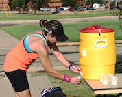 Heather Buchanan, Rotan fitness director, pours a cup of water after finishing the half marathon during the Dyess Mini Marathon at Dyess Air Force Base, Texas, Sept. 17, 2016. Buchanan placed first out of all the women who competed in the half marathon with the time 1:53:11. (U.S. Air Force photo by Senior Airman Kedesha Pennant)
