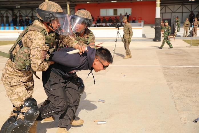 Mongolian Armed Forces soldiers detain a protester during a simulated riot for Non-Lethal Executive Seminar (NOLES) 2016 at the Five Hills Training Area, Mongolia, Sept. 21, 2016. Mongolian soldiers and National Police completed the final portion of the field training exercise for NOLES with several rehearsed scenarios. Non-lethal weapons are designed to incapacitate equipment and personnel while minimizing fatalities and permanent injury to personnel, and undesired collateral damage to property.