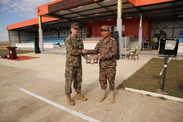 U.S. Marine 1st Lt. Michael McDonald, left, presents a plaque to Mongolian Armed Forces Maj. Gen. Sunkhbat Radnaabazar during Non-Lethal Executive Seminar (NOLES) 2016 at Five Hills Training Area, Mongolia, Sept. 21, 2016. McDonald is the officer in charge of the Marines participating in NOLES.Mongolian soldiers and National Police completed the final portion of the field training exercise for NOLES with several rehearsed scenarios. Both the United States and Mongolia have a continuing interest in strengthening their partnership with other Pacific nations, which will provide the cornerstone for security and stability in the region.