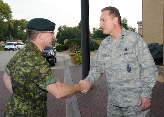 Maj. Gen. Charles Lamarre (left), Canadian Armed Forces Strategic Joint Staff director of staff, is greeted by Maj. Gen. Clinton E. Crosier, U.S. Strategic Command (USSTRATCOM) director of plans and policy, in front of USSTRATCOM headquarters, Offutt Air Force Base, Neb., Sept. 21, 2016. During his visit, Lamarre participated in discussions with USSTRATCOM leaders and subject matter experts on topics of mutual interest between the Canadian Department of National Defence and the Department of Defense. Lamarre also met with Adm. Cecil D. Haney, USSTRATCOM commander, and attended a series of briefings on the command's global strategic missions. One of nine DoD unified combatant commands, USSTRATCOM has global strategic missions assigned through the Unified Command Plan that include strategic deterrence; space operations; cyberspace operations; joint electronic warfare; global strike; missile defense; intelligence, surveillance and reconnaissance; combating weapons of mass destruction; and analysis and targeting. (USSTRATCOM photo by Steve Cunningham)
