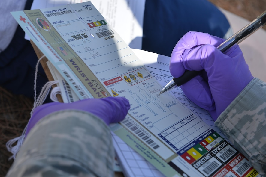 U.S. Air Force Tech. Sgt. Marinelle Bland, 39th Medical Operations Squadron medical admin, completes a triage tag during a mass casualty exercise Sept. 21, 2016, at Incirlik Air Base, Turkey. On the triage tag, Airmen identify and annotate patient injuries for further care. (U.S. Air Force photo by Senior Airman John Nieves Camacho)