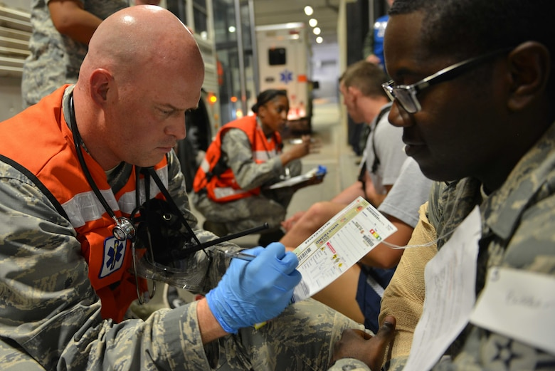 U.S. Air Force Capt. Benjamin Garman, 39th Medical Operations Squadron clinical nurse, annotates a simulated victim's conditions on a triage tag during a mass casualty exercise Sept. 21, 2016, at Incirlik Air Base, Turkey. Triage tags are used to identify conditions of injured individuals for medical personnel. (U.S. Air Force photo by Senior Airman John Nieves Camacho)