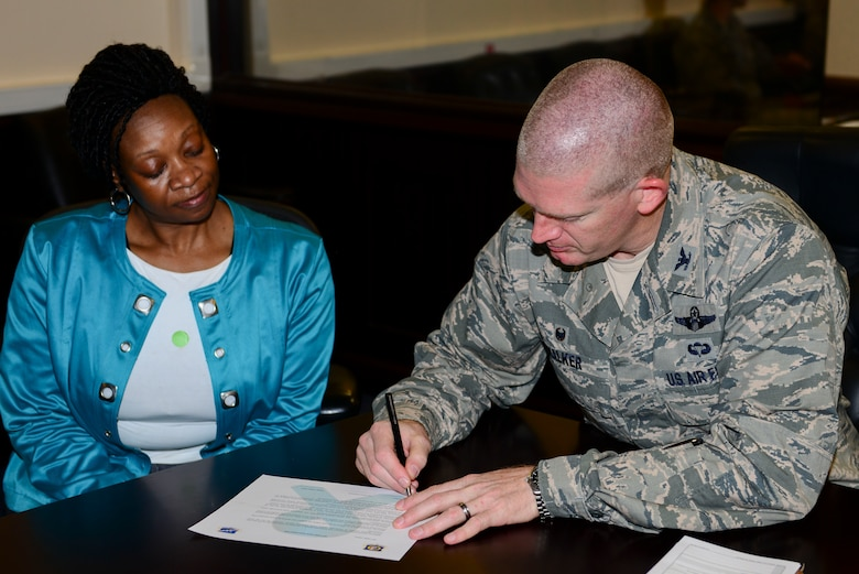 Shelia Bacon, 39th Air Base Wing sexual assault prevention and response (SAPR) victim advocate, oversees U.S. Air Force Col. John Walker, 39th ABW commander, as he signs the SAPR proclamation April 7, 2016, at Incirlik Air Base, Turkey. Bacon was selected as the U.S. Air Forces in Europe and Air Forces Africa 2016 National Image, Inc. Civilian Meritorious Service Award winner. (U.S. Air Force photo by Staff Sgt. Caleb Pierce/Released)