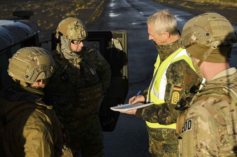 U.S. Air Force Airmen assigned to the 52nd Civil Engineer Squadron explosive ordnance disposal unit, Spangdahlem Air Base, Germany, talk with a German military observer during the Northern Challenge 16 exercise at Icelandic Coast Guard Keflavik Facility, Iceland, Sept. 19, 2016. During the exercise, 52nd EOD Airmen worked side by side with counterparts from allied and partner nations to become familiar with each other's military procedures and achieve greater interoperability in combating terrorism. (U.S. Air Force photo by Staff Sgt. Jonathan Snyder)