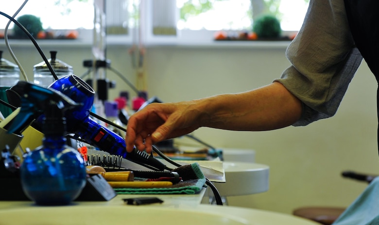 Claudia Gomez, barber, reaches for her array of barber tools as she cuts a customer's hair Sept. 20, 2016, at Ramstein Air Base, Germany. After working on Ramstein for 20 years and gaining confidence in her abilities, she became the owner of the barber shop in 2001. (U.S. Air Force photo/Airman 1st Class Lane T. Plummer)