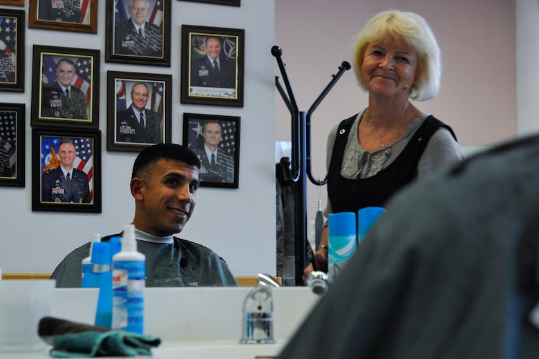 "Claudia Gomez, barber, shares a conversation with her customer, Airman 1st Class Hector Montoya, 721st Aerial Port Squadron passenger service agent, Sept. 20, 2016, at Ramstein Air Base, Germany. Gomez believes in recreating a ""close to home"" atmosphere with her shop, and enjoys getting to know the people that come in and helping them feel comfortable. (U.S. Air Force photo/Airman 1st Class Lane T. Plummer)"