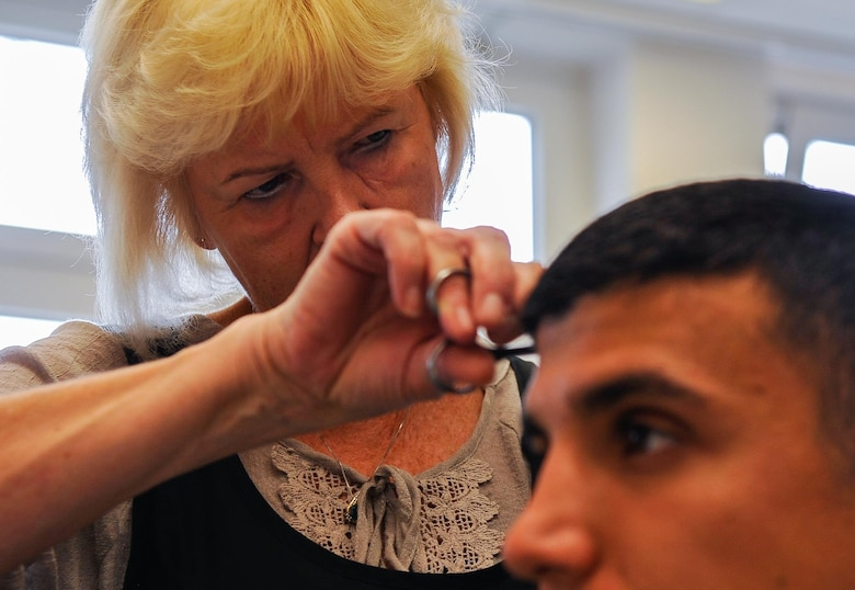 Claudia Gomez, barber, cuts Airman 1st Class Hector Montoya's hair, 721st Aerial Port Squadron passenger service agent, Sept. 20, 2016, at Ramstein Air Base, Germany. Gomez has cut hair for thousands of Airmen and families over the 35 years she's worked on base. (U.S. Air Force photo/Airman 1st Class Lane T. Plummer)