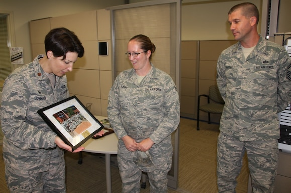 Maj. Melissa Johnson presents a special team photo to her outgoing 932nd Services Flight member, Senior Airman Jessica Busby, while Senior Master Sgt. Joseph Harter looks on as she moves to another unit.  (U.S. Air Force photo by Maj. Stan Paregien)