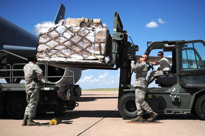 U.S. Air Force Airmen assigned to the 7th Logistics Readiness Squadron guide a Global Samaritan Resources' pallet of food onto a K loader at Dyess Air Force Base, Texas, Sept. 20, 2016. Global Samaritan Resources received donations and raised funds to donate fortified dehydrated food for distribution to Iraqi refugees. (U.S. Air Force photo by Airman 1st Class April Lancto)
