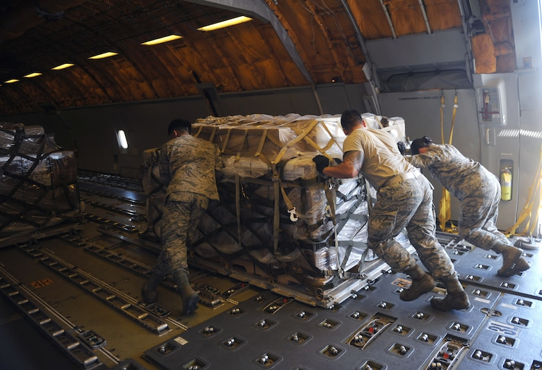 U.S. Air Force Airmen assigned to the 7th Logistics Readiness Squadron push a pallet of packed fortified dehydrated food into a KC-10 Extender at Dyess Air Force Base, Texas, Sept. 20, 2016. The shipment was the largest on record for Global Samaritan Resources for refuges in Iraq, equaling about 475,000 servings. (U.S. Air Force photo by Airman 1st Class Rebecca Van Syoc)