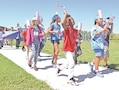 Aamirah Grantham (left) dances while waving her American flag Sept. 9, during Fort Riley Elementary School's Freedom Walk.