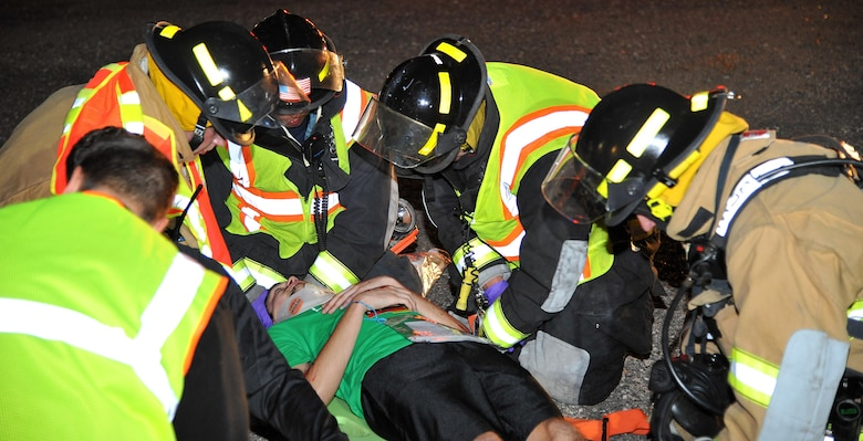 Grand Forks area firefighters practice rescue strategies and first aid procedures on a simulated plane crash victim during an exercise at the Grand Forks International Airport, N.D., Sept. 21, 2016. Grand Forks AFB firefighters joined area fire depts. and other first responders for a community effort to develop readiness for emergency response. (U.S. Air Force photo by Airman 1st Class Elijaih Tiggs)