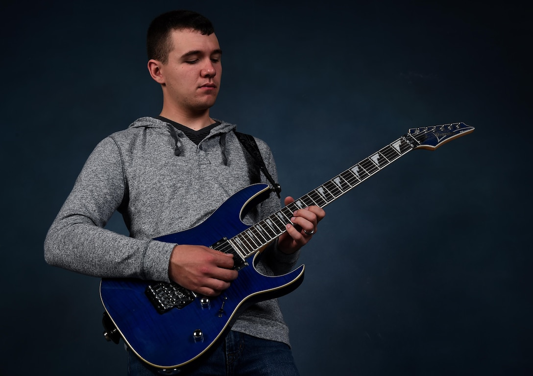 Airman 1st Class Zacary Heinzerling, 460th Security Forces Squadron apprentice, plays his guitar during a photoshoot September 8, 2016, at Buckley Air Force Base, Colo. In addition to the guitar, Heinzerling knows how to play the tuba, trombone, saxophone, piano, baritone and drums. (U.S. Air Force photo by Airman Holden S. Faul/ Released)