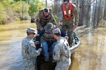 Louisiana National Guard soldiers with the 2225th Multi-Role Bridge Company, 205th Engineer Battalion, help a man out of the bridge erection boat they used to check on residents affected by flooding in Ponchatoula, La., March 13, 2016. Louisiana National Guard photo by 1st Lt. Rebekah Malone