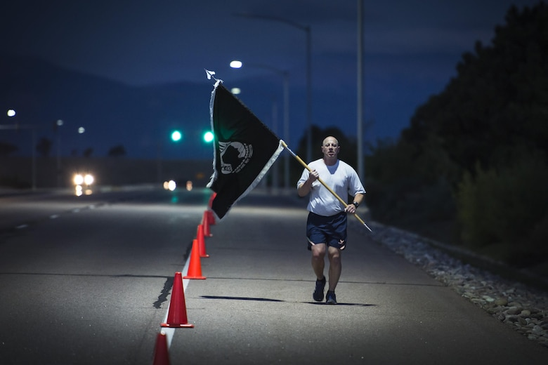 Peter Aronson, 19th Space Operations Squadron, runs alone with the prisoners of war and missing in action flag during the POW/MIA run at Schriever Air Force Base, Colorado, Thursday, Sept. 15, 2016. The flag was continuously carried for a full 24-hour period, even during the late night and early morning hours, symbolizing Schriever's dedication to honoring POW/MIA service members.(U.S. Air Force Photo/Dennis Rogers)