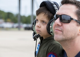 Jack Kirkbride and his dad watch an  A10 Thunderbolt II, from the 104th Fighter Wing, taxi at the Warfield Air National Guard Base in Middle River, Maryland, Sept. 17, 2016. The Pilot of the Day program was coordinated through the 175th Wing and the Gold in Fight Foundation.