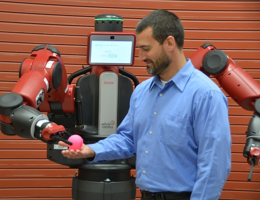 Dr. Joseph Lyons, Human Trust and Interaction Branch technical advisor, is given a ball by the Baxter robot after instructions were given to the robot by a member of Lyons' team. (U.S. Air Force photo / Gina Marie Giardina)