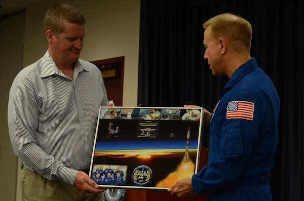 Defense Information School Public Affairs Officer, Joseph Coslett, (left) receiving signed poster by NASA astronaut Timothy Kopra (right) and Expedition 47 crew on Fort Meade, Md., Sept. 13, 2016. The poster shows his trip to space.
