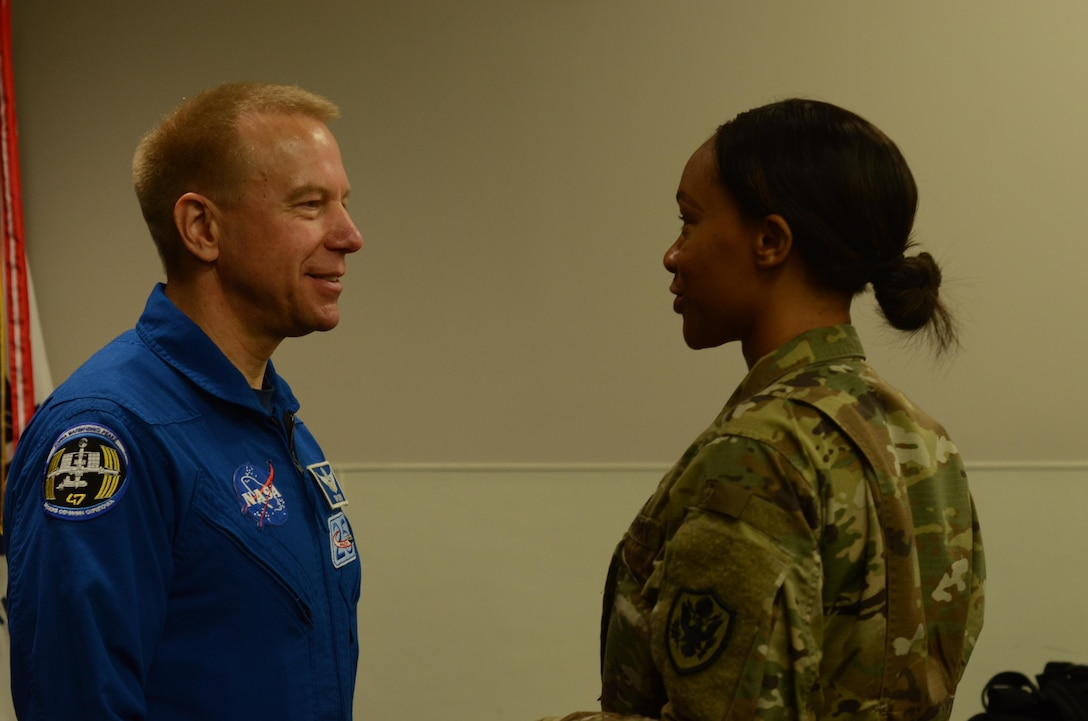 Staff Sgt. Candice Funchess (right), a Defense Information School journalism instructor, welcomes NASA astronaut Timothy Kopra (left) to the school on Fort Meade, Md., Sept. 13, 2016. Kopra's presentation unveiled his unique experiences aboard the International Space Station.