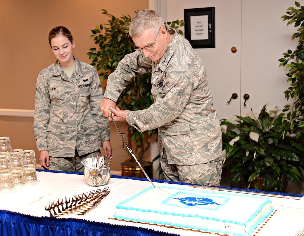 Retired Col. Steven Lamb, former 72nd Medical Group, makes the first slice of the cake at the Sept. 15 ceremony commemorating the Air Force's 69th birthday as the oldest active duty member. Airman Allison Lay, with the 552nd Maintenance Squadron, was the youngest attending member and made the second slice. (Air Force photo by Kelly White)