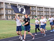 Chief Master Sgt. Roger Turnipseed, with the 552nd Aircraft Maintenance Squadron and also with the Tinker Chief's Group, passes the POW/MIA flag to a member of the 72nd Force Support Squadron during the 24-hour Vigil Run as part of Tinker's POW/MIA events. Members of Team Tinker took turns carrying the POW/MIA flag around the Tinker track from 7:30 a.m. Sept. 15 to 7:30 a.m. Sept. 16 when it was moved from the track to the POW/MIA Breakfast at the Tinker Club. The flag was then passed to the youngest Airman at the breakfast and posted at the front of the room during the ceremony. After the breakfast, the flag was handed off to participants of the POW/MIA Ruck March and carried for the entire 10K. Later that day, the flag was taken to the Del City American Legion and VFW Post 9969 for a POW/MIA Retreat Ceremony. At the retreat, it was announced that the flag had been moved by approximately 120 Airmen, civilians, contractors, and dependents for a total of 160.15 miles. (Air Force photo by Kelly White)