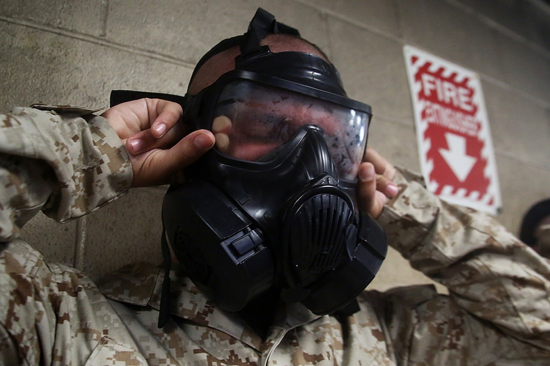 """Recruit Edwin Morales, Platoon 3090, Company M, 3rd Recruit Training Battalion, """"breaks the seal"""" on his M50 joint service general purpose mask while in the gas chamber aboard Page Field, Marine Corps Recruit Depot Parris Island, S.C. Morales was recruited by Staff Sgt. Mario Sanchez from Recruiting Substation Fort Myers, Recruiting Station Fort Lauderdale. Morales, a native of Cape Coral, Florida, joined the Marine Corps to become a combat engineer. (U.S. Marine Corps photo by Cpl. John-Paul Imbody/Released)"""