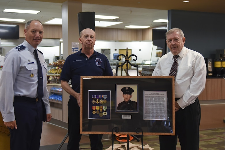 U.S. Air Force Col. Michael Downs, 17th Training Wing Commander, retired Chief Master Sgt. Ronald Graham and retired Master Sgt. Thomas Crowley, present a shadow box at the Cressman Dining Facility on Goodfellow Air Force Base, Sept. 22, 2016. The shadow box honored Sgt. Peter Cressman who was killed in action during a 6994th mission. (U.S. Air Force photo by Airman 1st Class Chase Sousa/Released)