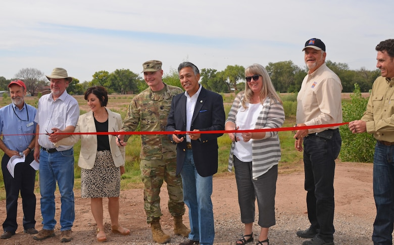 ALBUQUERQUE, N.M. – AMAFCA engineer Nolan Bennet (far right) holds the ribbon that (l-r): AMAFCA director Bruce Thomson; MRGCD director John Kelly; Rio Grande High School principal Amanda De Bell; Albuquerque District Commander Lt. Col. James Booth; Bernalillo County Commissioner Art De la Cruz; AMAFCA director Debbie Stover; and MRGCD chief engineer Mike Hamman prepare to cut, officially opening Pond 187, Sept. 20, 2016.