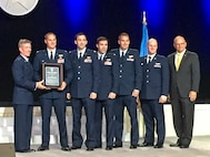 Gen. Herbert Carlisle (left), Air Combat Command commander, presents Lt. Col. Lucas Teel, 336th Fighter Squadron commander, and other members of the squadron with the David. C. Schilling Award at the annual Air, Space & Cyber Conference, Sept. 19, 2016, in National Harbor, Maryland. The award is sponsored by the Air Force Association and recognizes the most outstanding contribution to national defense in the field of flight, in the atmosphere or space, by either an Air Force military member, Department of the Air Force civilian, unit or group of individuals. (Courtesy photo)