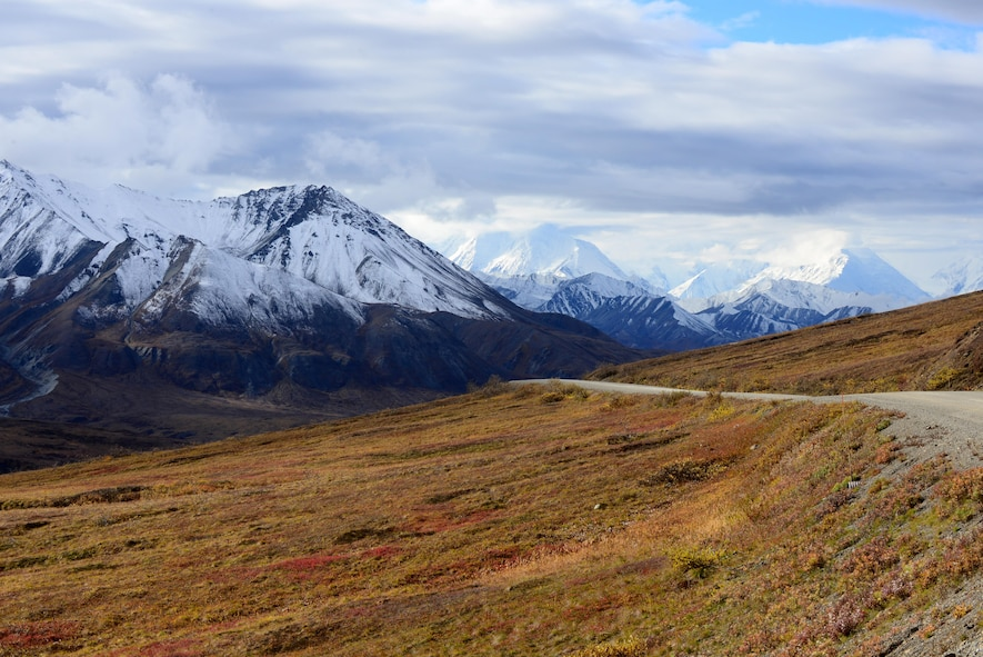 Mountains become visible through the clouds Sept. 20, 2016, in Denali National Park and Preserve, Alaska. This is only one of the many views of beautiful scenery offered on the drive through the park. (U.S. Air Force photo by Airman 1st Class Cassandra Whitman)