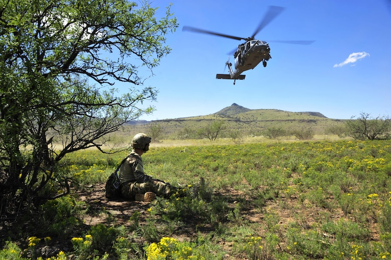 U.S. Air Force 1st Lt. Jaron Jablonski, 55th Rescue Squadron HH-60G Pave Hawk co-pilot, waits in concealment for rescue assets to arrive during a search and rescue exercise at Outlaw/Jackal military operations area in southeastern Ariz., Sept. 15, 2016. During the exercise, Jablonski played a simulated downed pilot with broken legs. During the extraction, an HH-60G Pave Hawk from the 55th Rescue Squadron was required to hover as close as possible in order to rescue Jablonski. (U.S. Air Force photo by Senior Airman Cheyenne A. Powers)