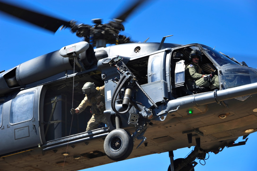Members from the 55th Rescue Squadron hoist a simulated down pilot off the ground into an HH-60G Pave Hawk during a search and rescue exercise at Outlaw/Jackal military operations area in southeastern Ariz., Sept. 15, 2016. During the exercise, rescue assets remained in constant communication with the downed pilot to execute a successful extraction. (U.S. Air Force photo by Senior Airman Cheyenne A. Powers)