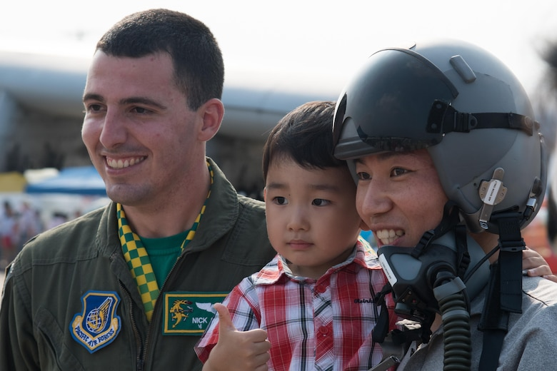 U.S. Air Force 1st Lt. Nick Castle, 25th Fighter Squadron pilot, poses for a photo with a family during Air Power Day 2016 at Osan Air Base, Republic of Korea, Sept. 24, 2016. The air show highlighted performances of many different aircraft including the Republic of Korea air force Black Eagles. (U.S. Air Force photo by Senior Airman Dillian Bamman)