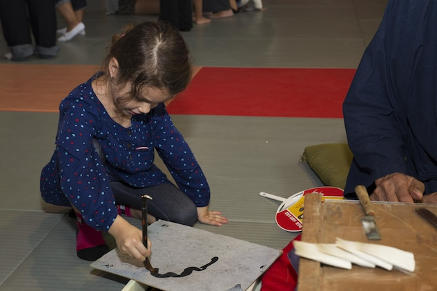 Joannabella Smith, a Marine Corps Air Station Iwakuni resident, practices her calligraphy at the Kumano Brush Festival in Kumano, Japan, Sept. 22, 2016. Air station residents traveled to Kumano with the Cultural Adaptation Program for the Kumano Brush Festival, where they were given an opportunity to participate in a calligraphy competition with the Japanese locals. After attending the festival the residents visited the Fudenosato Kobo Museum where they learned how calligraphy equipment is made. (U.S. Marine Corps photo by Lance Cpl. Joseph Abrego)