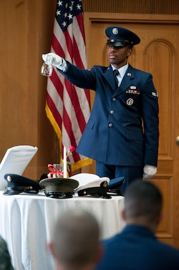 U.S. Air Force Airman 1st Class Colin Jeffers, 51st Force Support Squadron services journeyman, inverts an empty glass during the opening ceremony of a POW/MIA memorial service at Osan Air Base, Republic of Korea, Sept. 15, 2016. The event honors missing service members and the U.S. government's continued responsibility to locate prisoners of war. (U.S. Air Force photo by Staff Sgt. Jonathan Steffen)