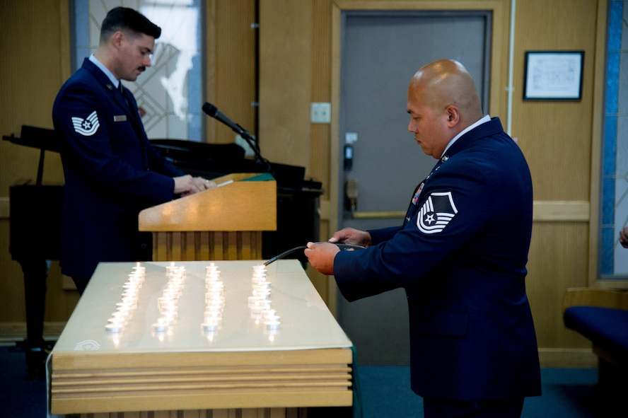 U.S. Air Force Master Sgt. Philip Quinn-Narcis, 51st Civil Engineer Squadron assistant chief of fire operations, lights a candle during a POW/MIA memorial service at Osan Air Base, Republic of Korea, Sept. 15, 2016. POW/MIA Remembrance Day is traditionally observed on the third Friday of September each year.(U.S. Air Force photo by Staff Sgt. Jonathan Steffen)