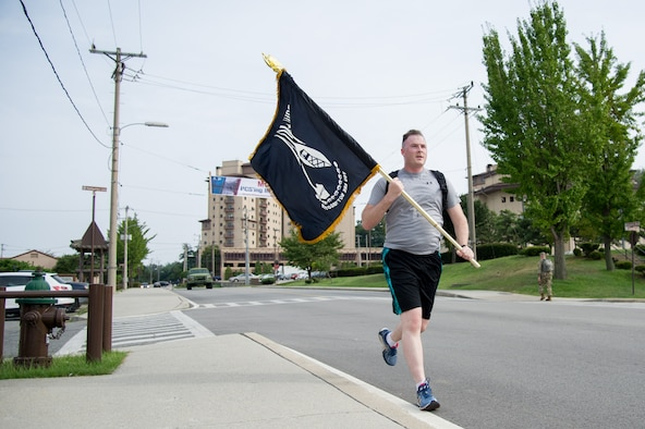 U.S. Air Force Staff Sgt. Joel, 6th Intelligence Squadron, carries a flag during a POW/MIA 24 hour remembrance run at Osan Air Base, Republic of Korea, Sept. 15, 2016. The flag stayed in motion for 24 hours to pay respect and honor those service members are that are still missing. (U.S. Air Force photo by Staff Sgt. Jonathan Steffen)