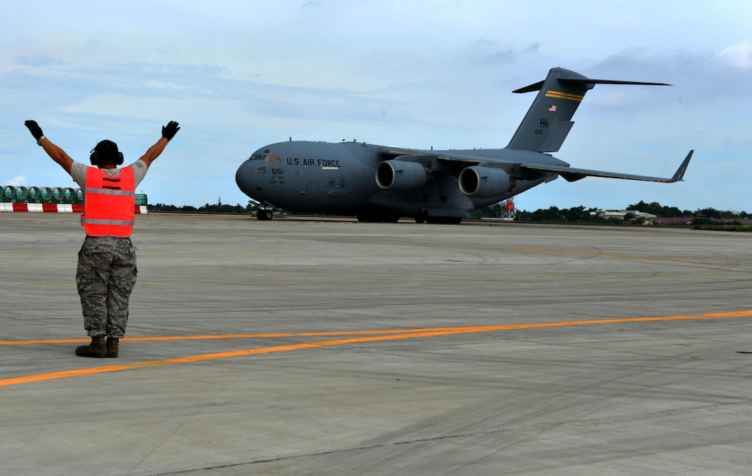 A U.S. Air Force member marshals a U.S. Air Force C-17 to its designated ramp position at Mactan Air Base, Philippines, Sept. 24, 2016. The military members were in Mactan in support of U.S. Pacific Command's ongoing Air Contingent mission. The goal of the rotation is for Philippine military and civilian leaders to work with their U.S. counterparts to improve airlift capabilities across the spectrum of military operations and to solidify long-standing relationships in the region. (U.S. Air Force photo by Capt. Mark Lazane)