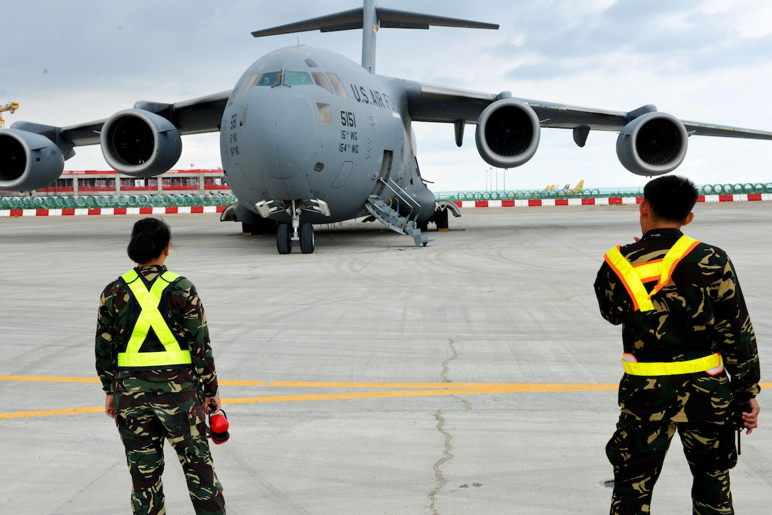 Members of the Philippines Air Force observe a U.S. Air Force C-17 at Mactan Air Base, Philippines, Sept. 24, 2016. The military members were in Mactan in support of U.S. Pacific Command's ongoing Air Contingent mission. The goal of the rotation is for Philippine military and civilian leaders to work with their U.S. counterparts to improve airlift capabilities across the spectrum of military operations and to solidify long-standing relationships in the region. (U.S. Air Force photo by Capt. Mark Lazane)