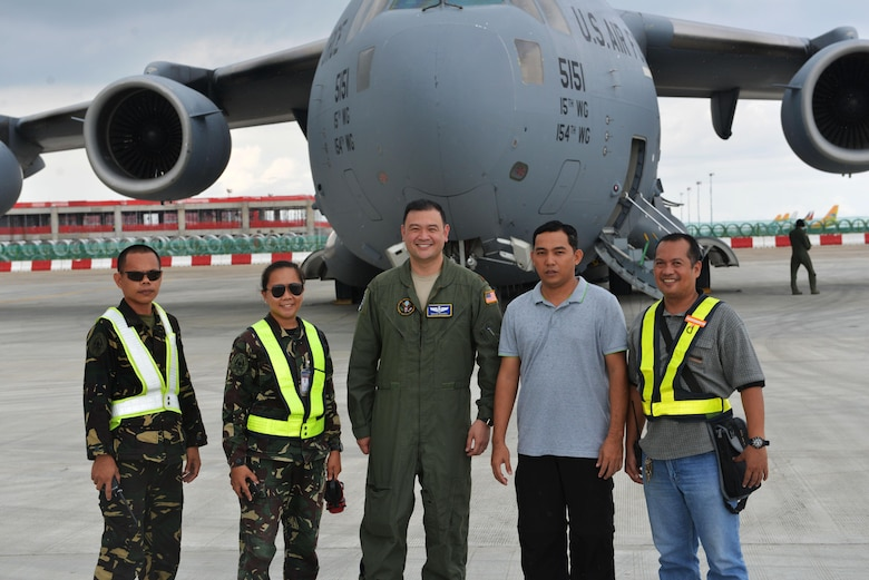Members of the Philippines Air Force stand with U.S. Air Force Maj. Brian Barba, Joint U.S. Military Assistance Group Chief of Air Operations, in front of a U.S. Air Force C-17 at Mactan Air Base, Philippines, Sept. 24, 2016. The military members were in Mactan in support of U.S. Pacific Command's ongoing Air Contingent mission. The goal of the rotation is for Philippine military and civilian leaders to work with their U.S. counterparts to improve airlift capabilities across the spectrum of military operations and to solidify long-standing relationships in the region. (U.S. Air Force photo by Capt. Mark Lazane)