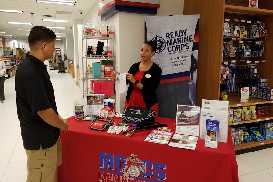 Zeyna Anderson, a trainer with Marine Corps Family Team Building, discusses how to make an emergency plan during a Marine Corps community services outreach event.
