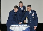 DLA Director Lt. Gen. Andy Busch (center); Capt. Shane Perry (left), the youngest airmen attending; and Col. John Martin, the oldest airman attending as a guest, use a sword to cut the Air Force birthday cake at a Sept. 22 celebration.