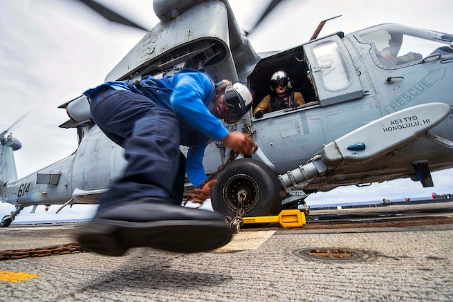 Navy Petty Officer 3rd Class Demetrice Cox secures an MH-60s Seahawk helicopter with chocks and chains on the USS Chancellorsville during Valiant Shield 2016 in the Philippine Sea, Sept. 22, 2016. The biennial exercise focuses on joint training among U.S. forces. Navy photo by Petty Officer 2nd Class Andrew Schneider