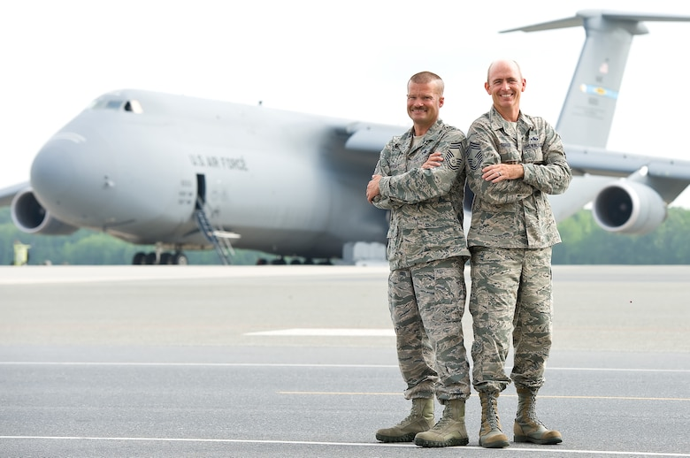 Chief Master Sgts. Robert Wright (left), 436th Maintenance Group, and Bryan Ford, 512th Maintenance Group, stand together July 3, 2013, on the flightline of Dover Air Force Base, Del., where they first began working with each other in 1994, after having known each other through their high school years in Virginia during the mid-1980s. Wright and Ford, an active-duty and reserve Airman, teamed together and led numerous Total Force Initiatives for the Air Force and Air Force Reserve. Since the photo was taken, Wright has retired but still serves on base as a contractor. (U.S. Air Force photo by Roland Balik)