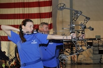 U.S. Air Force Senior Airman, KeiLani Vessar, 55th Medical Operations Squadron, and U.S. Air Force (retired) Pete Plaza, take aim with their bows during an archery exercise. Wounded warriors members from across the country participated in a special camp focused on recovery. More than 120 participated in hopes to aid with their healing process with events like archery, swimming, basketball and more at Offutt Air Force Base, Nebraska, Sept. 17 - 23. (U.S. Air Force photo by Jeff W. Gates)