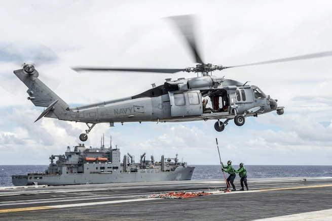 Sailors attach cargo pendants to an MH-60S Seahawk on the USS Ronald Reagan during a vertical replenishment with the Military Sealift Command dry cargo and ammunition ship USNS Charles Drew as part of Exercise Valiant Shield 2016 in the Philippine Sea, Sept. 23, 2016. Navy photo by Petty Officer 3rd Class Nathan Burke