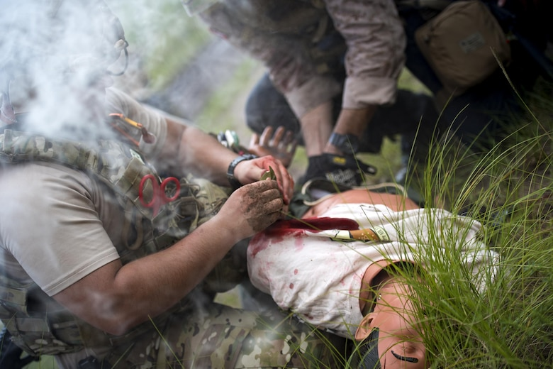 U.S. Air Force Senior Airman Michael Triana, left, 347th Operations Support Squadron independent duty medical technician-paramedic, addresses injuries on a simulated patient during a tactical combat casualty care course, Sept. 22, 2016, in Okeechobee, Fla. TCCC tests and reinforces participants' lifesaving medical skills while they are in high-stress, combat scenarios. (U.S. Air Force photo by Staff Sgt. Ryan Callaghan)